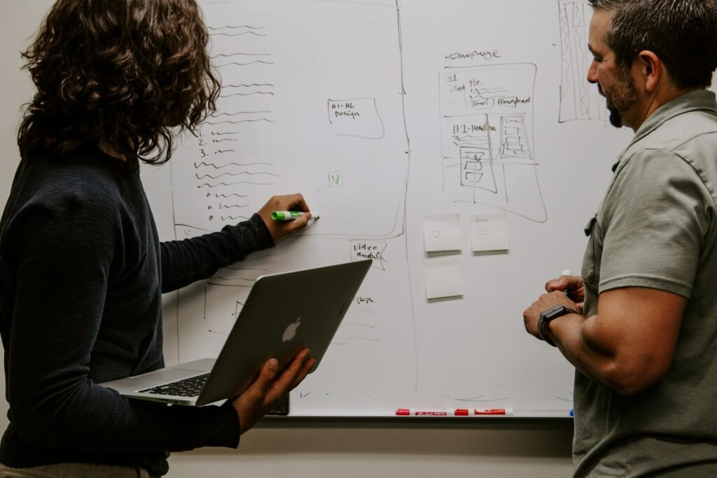 two people looking at marketing strategy on a board.